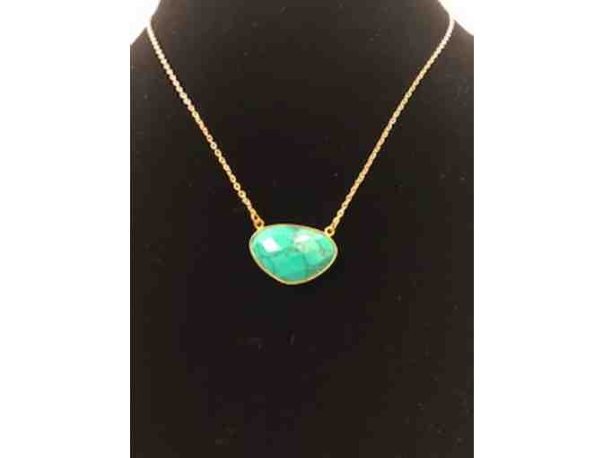 Turquoise colored pendant on  gold tone chain